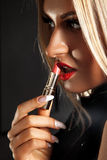 Portrait of a beautiful young blonde that paints red lipstick Stock Image