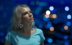 Portrait of beautiful young blonde in the turquoise shirt on the background of night city lights. Modern style Royalty Free Stock Images