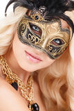 Portrait of Beautiful young blonde woman in black and gold mysterious venetian mask. Fashion photo on white background royalty free stock image