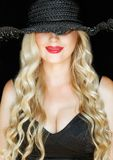 Portrait. Beautiful young blonde woman in black hat with a decollete on dark background smiling mysteriously. royalty free stock photos