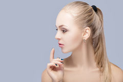 Portrait of beautiful young blonde woman with blue eyes on grey background. girl with clean skin Royalty Free Stock Photography