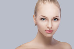 Portrait of beautiful young blonde woman with blue eyes on grey background. girl with clean skin Royalty Free Stock Images