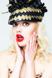 Portrait of beautiful young blonde woman in extravagant hat on white background Stock Photos