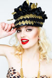 Portrait of beautiful young blonde woman in extravagant hat on white background Stock Images