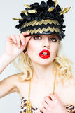 Portrait of beautiful young blonde woman in extravagant hat on white background Royalty Free Stock Photo