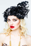 Portrait of beautiful young blonde woman in extravagant hat on white background Stock Photo