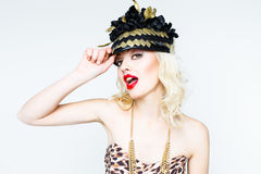Portrait of beautiful young blonde woman in extravagant hat on white background Stock Image