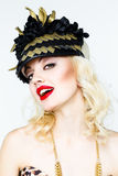 Portrait of beautiful young blonde woman in extravagant hat on white background Royalty Free Stock Photography