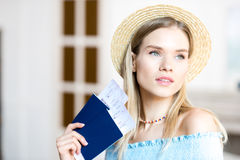 Portrait of beautiful young blonde woman in hat holding passports and tickets. Getting ready to travel concept Royalty Free Stock Image