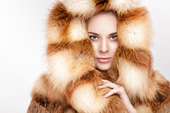 Portrait of beautiful young blonde woman in luxury Fox fur coat. Stock Images
