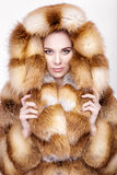 Portrait of beautiful young blonde woman in luxury Fox fur coat. Stock Photos