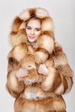 Portrait of beautiful young blonde woman in luxury Fox fur coat. Royalty Free Stock Photography