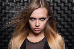 Portrait of a beautiful young blonde woman. Posing in a studio dressed in a black leather suit stock photo