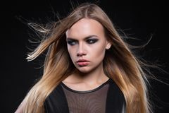 Portrait of a beautiful young blonde woman. Posing in a studio dressed in a black leather suit royalty free stock images