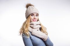 Portrait of beautiful young blonde woman wearing warm knitted sweater, hat, scarf and mittens on white background. Happy smiling girl looking at camera. Winter stock images