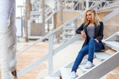Portrait of a beautiful young blonde woman who poses on camera on the street royalty free stock photos