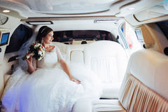 Portrait of a beautiful young bride in the car Stock Photos