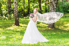 Portrait of beautiful young  bride in elegant white dress with long veil outdoors Stock Images