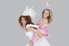 Portrait of beautiful young bride giving piggyback ride to bridesmaid over gray background Stock Images