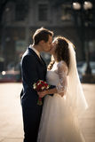 Portrait of beautiful young bride and groom kissing on street Stock Images