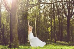 Portrait of a beautiful young bride sitting alone on swing outdoors Royalty Free Stock Photography