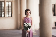 Portrait of a beautiful young bride that stands between the columns near old building and holding bridal bouquet Stock Photo