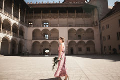 Portrait of a beautiful young bride that stands between the columns near old building and holding bridal bouquet Royalty Free Stock Image