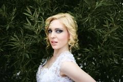 Portrait beautiful young bride in white dress in summer green park Royalty Free Stock Photo