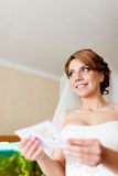 Portrait of a beautiful young bride who is reading a letter from the bridegroom Stock Photo