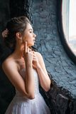 Portrait of a beautiful young bride at the window royalty free stock images