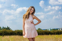 Portrait of a beautiful young brown-haired woman. On a background of nature and blue sky with clouds Royalty Free Stock Image
