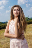 Portrait of a beautiful young brown-haired woman. On a background of nature and blue sky with clouds Royalty Free Stock Images