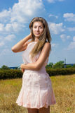 Portrait of a beautiful young brown-haired woman. On a background of nature and blue sky with clouds Stock Photo
