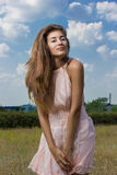 Portrait of a beautiful young brown-haired woman. On a background of nature and blue sky with clouds Royalty Free Stock Photos