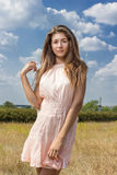 Portrait of a beautiful young brown-haired woman. On a background of nature and blue sky with clouds Stock Photography