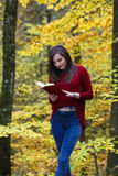 Portrait of beautiful young brunette girl reading a book in the. Park at fall Stock Images