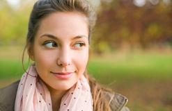Portrait of beautiful young brunette outdoors. Beautiful young brunette taking a sideways glance, outdoors autumn park Royalty Free Stock Image