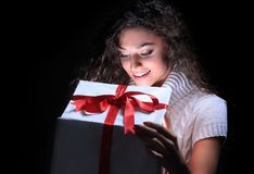 Portrait of a beautiful young brunette peering in a gift box. Happy young woman opening a Christmas gift black background Royalty Free Stock Images
