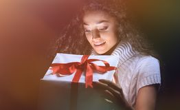 Portrait of a beautiful young brunette peering in a gift box. Happy young woman opening a Christmas gift black background Stock Photography