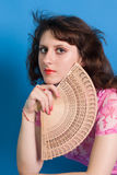 Young brunette in a pink dress on a  blue background Stock Images