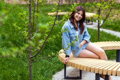 Portrait of beautiful young brunette woman in blue casual denim style sitting and looking at camera with toothy smile. Outdoor spring or summer day shot royalty free stock image
