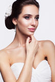 Portrait of beautiful young brunette woman bride in white Weddin. Portrait of beautiful young brunette woman bride with hand near face in white Wedding Dress on Royalty Free Stock Image