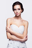 Portrait of beautiful young brunette woman bride in white Weddin. G Dress with hands crossed on light gray background Royalty Free Stock Photos