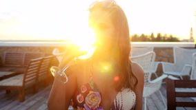 Portrait of beautiful young brunette woman drinking wine outdoors cafe at the sunshine during sunset with lense flare. Effects in summer time. 3840x2160. 4k stock video footage