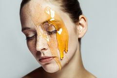 Portrait of beautiful young brunette woman with freckles and honey on face with closed eyes and serious face stock photo