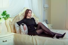 Portrait of beautiful young brunette woman sitting in bedroom Royalty Free Stock Images