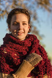 Portrait of a beautiful young brunette woman in a red poncho Royalty Free Stock Photography