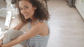 Portrait of a beautiful young woman smiling at the camera in a kitchen. stock video footage