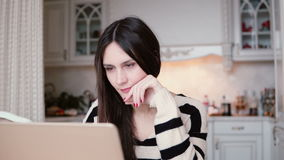 Portrait of a beautiful young brunette woman uses laptop in a bright dining. stock video footage