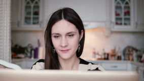 Portrait of a beautiful young brunette woman uses laptop in a bright dining. stock footage